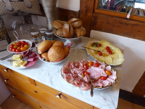 Breakfast buffet with buns, sausage, cheese, jam and fresh tomatoes.