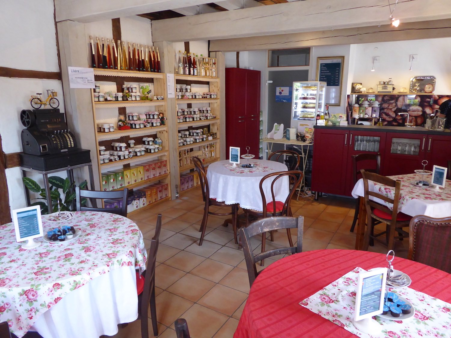 Interior view of the coffee shop inside the farmhouse, capturing the rustic ambience. In the background goods which can be bought to take away are showcased in shelf.