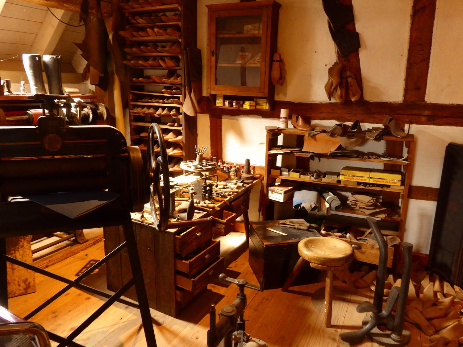 Picture of the exhibition room - old shoemaker workshop. Authentical tools and materials are in place so vsitors can imagine how the workshop was looking back in the days.
